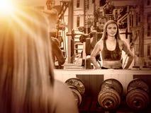 Женщины и люди с гантелями на спортзале Стоковые Изображения