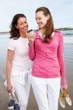 2 женщины идя вдоль пляжа смотря мобильный телефон Стоковые Фотографии RF