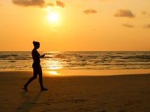 Женщины идя на пляж на времени захода солнца силуэт gir Стоковые Изображения