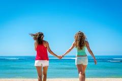 2 женщины идя прочь к океану Стоковое фото RF