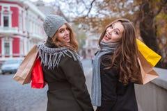 2 женщины идя с хозяйственными сумками outdoors Стоковые Фотографии RF