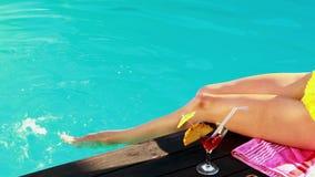 Женщины качая ее ноги в бассейне с коктеилем акции видеоматериалы