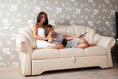 Женщины кладя на софу стоковые фото