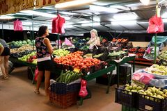 Женщины клиент и продавец стоя около стойки свежих овощей и плодоовощей стоковая фотография