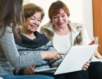 Женщины милой девушки уча усмехаясь старшие используя компьтер-книжку Стоковое Изображение