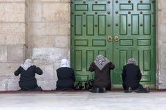 4 женщины молят на их коленях перед зеленой закрытой дверью старого купола мечети утеса в мусульманском квартале  стоковое фото rf