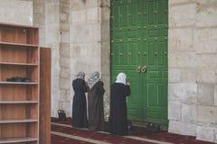 4 женщины молят на их коленях перед зеленой закрытой дверью старого купола мечети утеса в мусульманском квартале  стоковое изображение rf