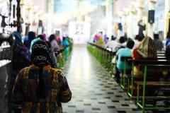 Женщины моля бога в пасторе церков и боге людей моля в церков стоковые изображения rf