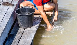 Женщины моя одежды в реке стоковая фотография