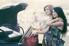 2 женщины моды с хозяйственными сумками на автостоянке автомобиля Стоковые Изображения