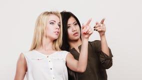 2 женщины моды указывая палец острословия Стоковая Фотография