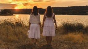 2 женщины наблюдая заход солнца с белыми платьем и фонариком стоковые изображения rf
