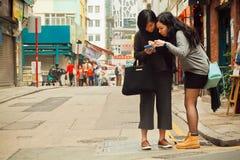 2 женщины наблюдая сотовый телефон для того чтобы найти путь в большом городе Стоковое фото RF