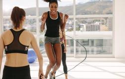 Женщины наслаждаясь разминкой скача веревочки на спортзале Стоковая Фотография