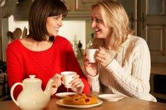 Женщины наслаждаясь чаем и тортом совместно Стоковое Фото