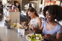 2 женщины наслаждаясь датой обеда в ресторане деликатеса Стоковая Фотография