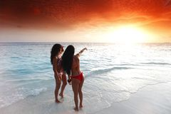 2 женщины наслаждаясь заходом солнца на пляже Стоковые Изображения