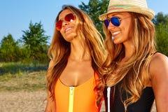 2 женщины наслаждаясь праздником пляжа Стоковые Изображения