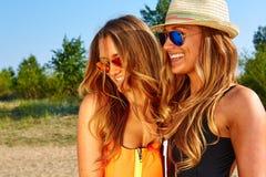2 женщины наслаждаясь праздником пляжа Стоковое Изображение