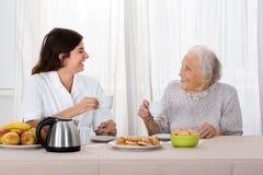 2 женщины наслаждаясь чаем и печеньями Стоковое Изображение RF
