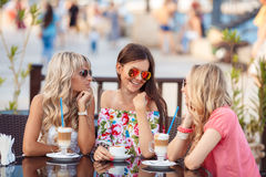 3 женщины наслаждаясь чашкой кофе в кафе Стоковая Фотография RF