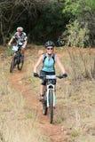 Женщины наслаждаясь outdoors ездой на гонке горного велосипеда Стоковое Изображение