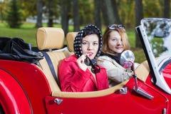 Женщины на автомобиле смотрят заинтересованными и удовлетворенными Стоковое Фото