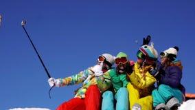 4 женщины на верхней части горы Примите selfie Праздник, потеха Костюмы горных лыж цвета Съемка замедления сток-видео