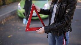 2 женщины на зеленом автомобиле поразили колесо и устанавливают непредвиденный знак на дорогу видеоматериал