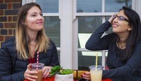 2 женщины на кафе улицы - иметь потеху Стоковое фото RF