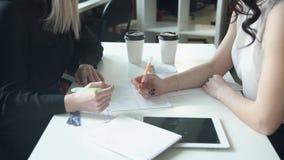 2 женщины на таблице на бумаге написанной совместно регулируют схему сток-видео