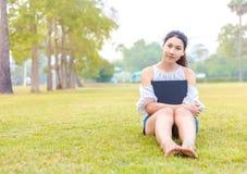 Женщины на траве и красивый она читая книгу Стоковые Изображения
