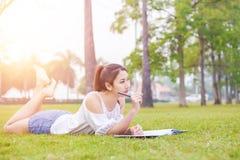 Женщины на траве и красивый она читая книгу Стоковые Фотографии RF