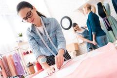3 женщины на фабрике одежды Они делают измерения и делают вырез стоковое изображение rf