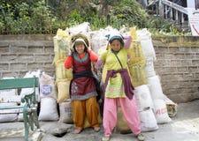 Женщины непальца Wo работая как цементы нося увиденные портером в сумке реднины стоковая фотография