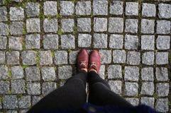 Женщины ног в ботинках на дороге Стоковая Фотография