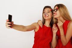 2 женщины нося красное платье принимая selfie Стоковые Изображения RF