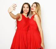 2 женщины нося красное платье принимая selfie Стоковая Фотография RF
