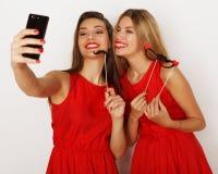 2 женщины нося красное платье принимая selfie Стоковая Фотография