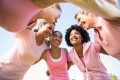 Женщины нося пинк для рака молочной железы с оружиями вокруг Стоковое Изображение
