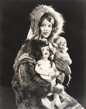 Женщины нося эскимосскую меховую шыбу держа куклы Стоковые Фотографии RF