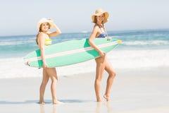 2 женщины нося surfboard на пляже Стоковые Фото