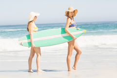 2 женщины нося surfboard на пляже Стоковая Фотография