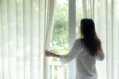 Женщины образа жизни раскрывают окно после для того чтобы получить, что вверх по белой кровати в восходе солнца утра ослабили нас стоковые изображения