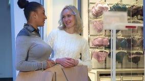 Женщины обсуждают бюстгальтеры и трусы около женское бельё ходят по магазинам стоковые фото