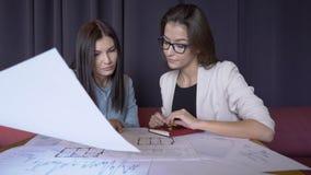 2 женщины обсуждают светокопию пока сидящ в современном офисе акции видеоматериалы