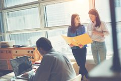 2 женщины обсуждая маркетинговый план в офисе деятельность человека компьтер-книжки Coworking и офис открытого пространства Стоковое Изображение RF