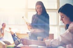 2 женщины обсуждая новый проект Startup команда в офисе просторной квартиры Влияние фильма, расплывчатая предпосылка Стоковое фото RF