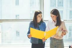 2 женщины обсуждая новый рабочий план в офисе Большое яркое окно позади Стоковые Изображения