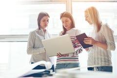 Женщины обсуждая проект в офисе Компьтер-книжка и таблетка, комната открытого пространства Стоковые Изображения RF